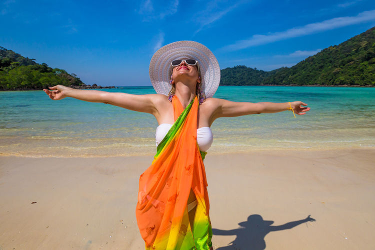 Back of happy and fashionable tourist woman with colorful sarong in turquoise water of Maya Bay famous lagoon of The Beach movie, Phi Phi Leh, Andaman Sea in Thailand Fashionable and happy tourist with sarong and pink wide-brimmed hat making a selfie on tropical famous beach of Nai Harn Beach, Rawai, Phuket, Thailand. Happy tourist enjoys panorama from Sail Rock View Point of kor 8 of Similan Islands National Park, Phang Nga, Thailand, one of the tourist attraction of the Andaman Sea. Happy woman with bikini and shorts, jumping in the air on Ya Nui Beach, a little cove divided by a rocky cape, Phuket, Thailand, Asia. Happy Koh Rok Islands Nui Beach Phang Nga Bay Phuket Thailand Tanning ☀ Thailand Vacations Woman Beach Beautiful Woman Beauty Beauty In Nature Day Girl Hat Koh Rok Leisure Activity Lifestyles Nature One Person Outdoors Phang Nga Rawai Real People Sand Scenics Sea Seascape Sky Standing Sun Hat Sunlight Surin Islands Travel Destinations Vacations Water Women Young Adult Young Women