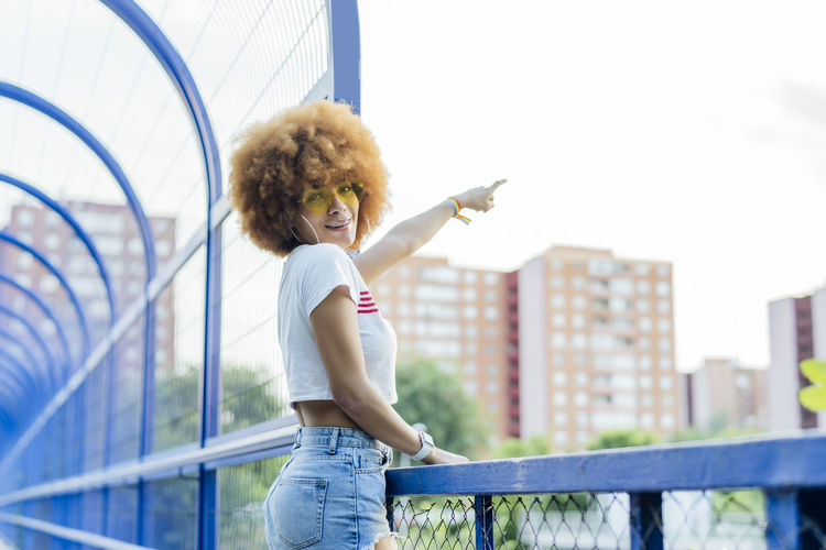 Full length of woman standing against railing