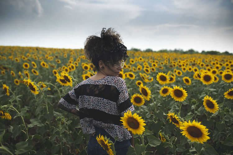 Beauty In Nature Casual Clothing Child Childhood Field Flower Flower Head Flowering Plant Freshness Growth Innocence Land Leisure Activity Nature One Person Outdoors Plant Real People Sky Sunflower Three Quarter Length Yellow