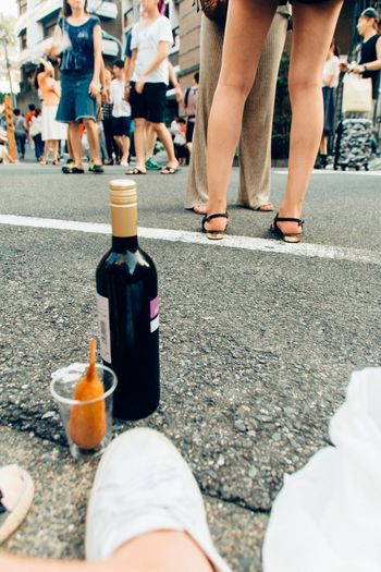 Close-Up Of Bottle On Ground With People In Distance