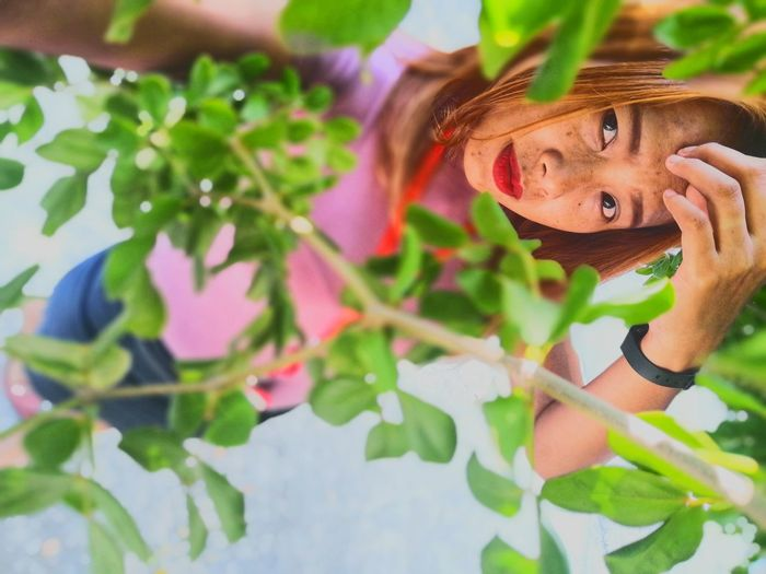 Portrait of young woman with plants