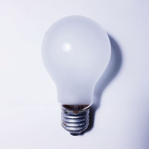 Close-up of light bulb against white background