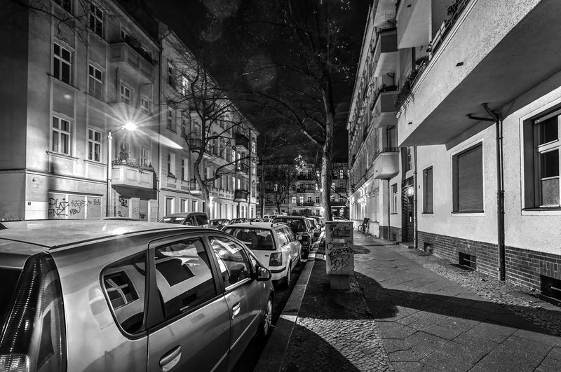 Cars on street amidst buildings in city at night