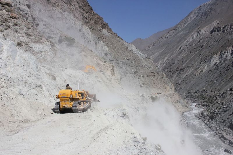 Rear View Of Manual Worker Driving Bulldozer At Construction Site On Mountain