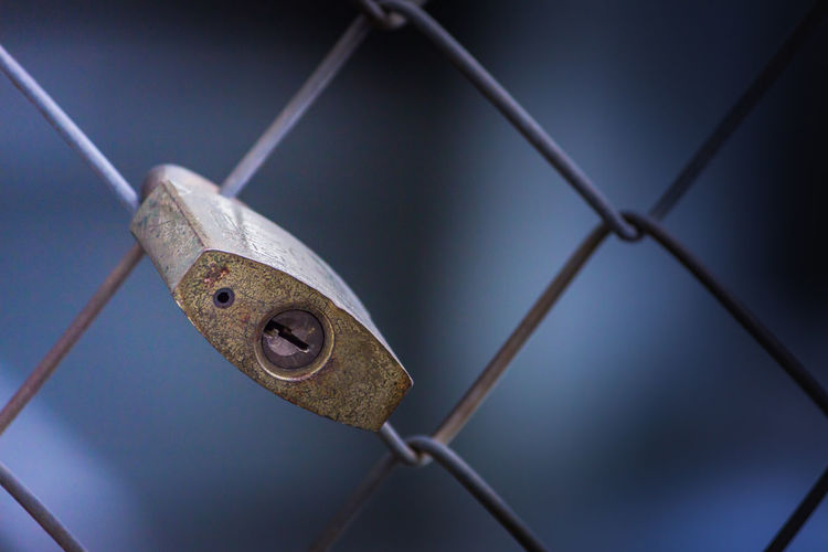 Close-Up Of Padlock Hanging On Fence