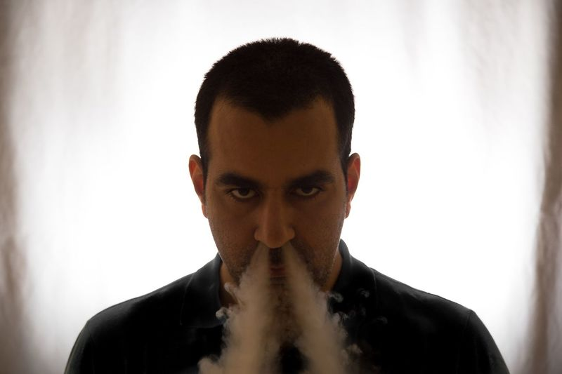 Close-up portrait of man exhaling smoke from nose