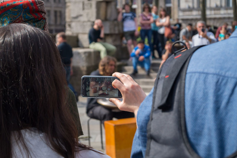 Rear View Of Woman Photographing People At Street