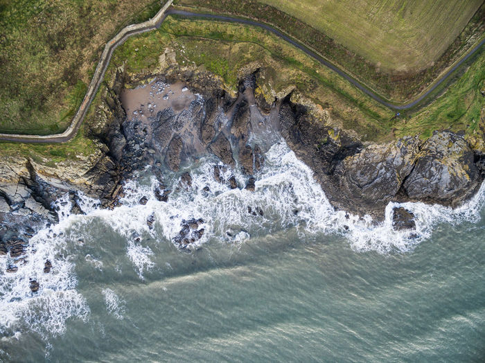 An aerial view of water meeting a cliff in the UK. Water Motion Nature Beauty In Nature Scenics - Nature Day No People Environment Outdoors Land Sea Plant Landscape Blurred Motion Rock Solid High Angle View Rock - Object Flowing Water Flowing Power In Nature Aerial View Drone Shot Cliff Landmeetssea