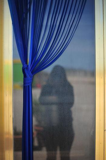 Rear view of woman seen through glass window