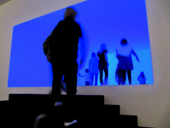 Silhouette people standing against blue wall
