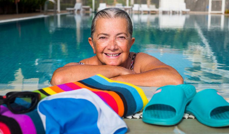 Portrait of smiling senior woman in swimming pool