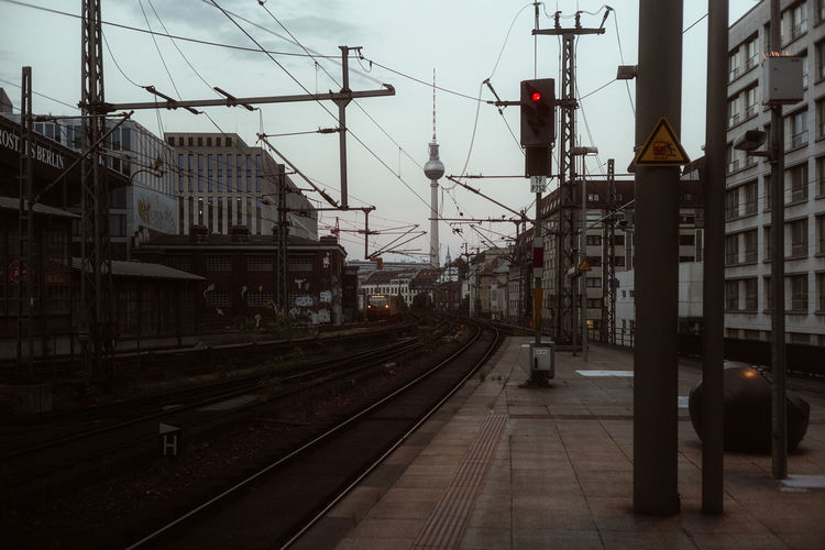 Railroad tracks by buildings in city against sky