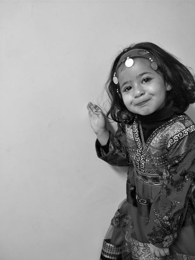 Portrait of cute girl in costume standing against wall