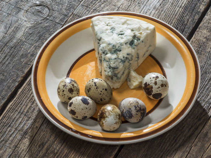 Quail eggs and roquefort cheese on a plate on an old wooden weathered table Wooden Quail Eggs Weathered Blue Cheese Close-up Day Directly Above Food Food And Drink Freshness Healthy Eating High Angle View Indoors  No People Old Old Buildings Plate Ready-to-eat Roquefort Table Wood - Material