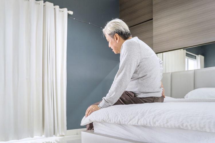 Senior man sitting on bed at home