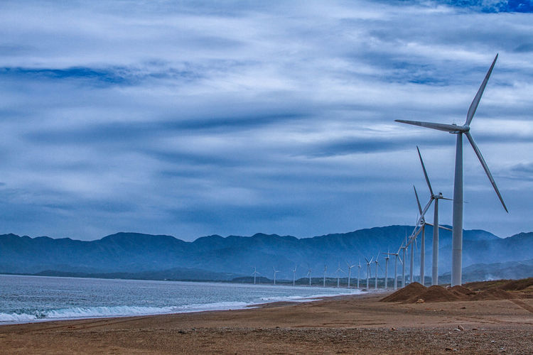 Alternative Energy Beach Cloud - Sky Day Industrial Windmill Mountain Mountain Range No People Outdoors Renewable Energy Sand Sea Sky Water Wind Power Wind Turbine Windmill