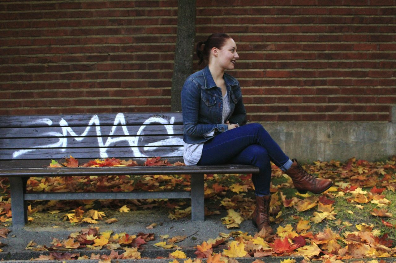 Thoughtful Woman Sitting On Bench Against Brick Wall At Park