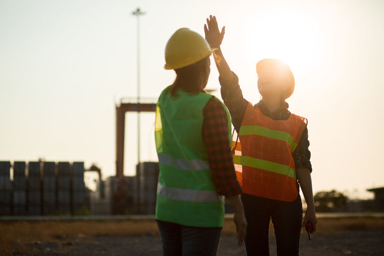 Rear view of men working against sky during sunset