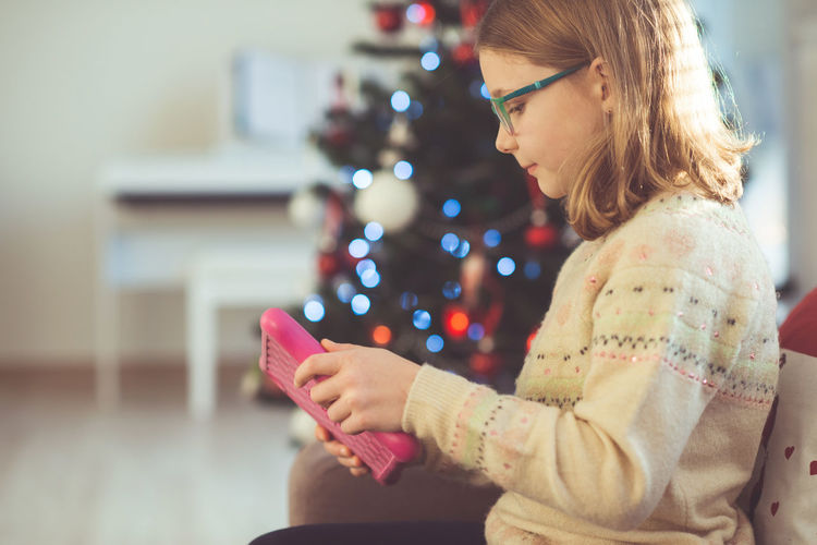 Girl using digital tablet at home during christmas