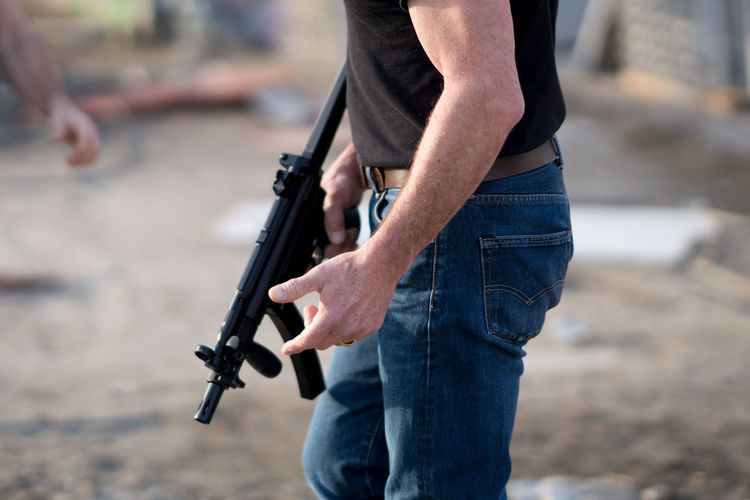 Midsection Of Man With Rifle Standing On Ground