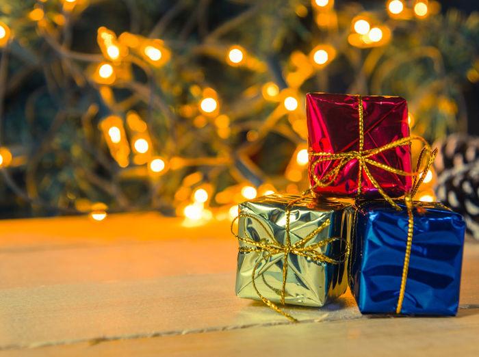 Close-up of christmas present against illuminated lights