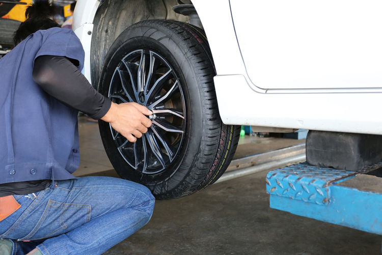 mechanic repaired wheeled vehicles in the garage. One Person Mode Of Transportation Transportation Real People Wheel Tire Land Vehicle Men Day Motor Vehicle Low Section Car Holding Casual Clothing Occupation Repairing Outdoors Lifestyles Midsection Jeans Mechanic Mechanic Mechanical Mechanics Mechanical Engineering