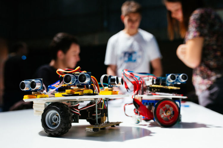 Close-up of remote controlled car with friends standing in background