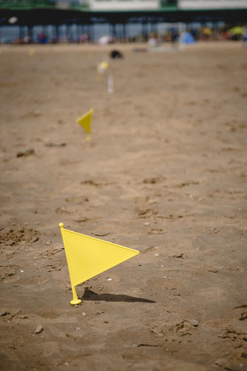 Close-up of arrow sign on sand