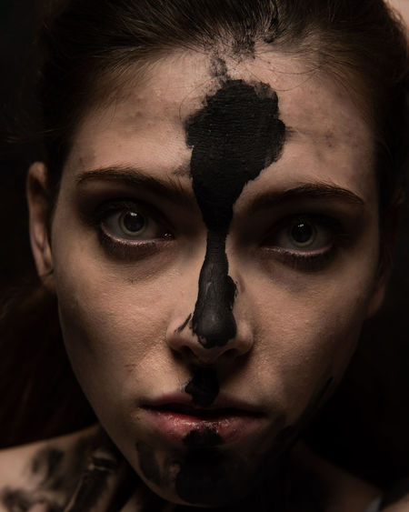 Close-up portrait of woman with black paint on face