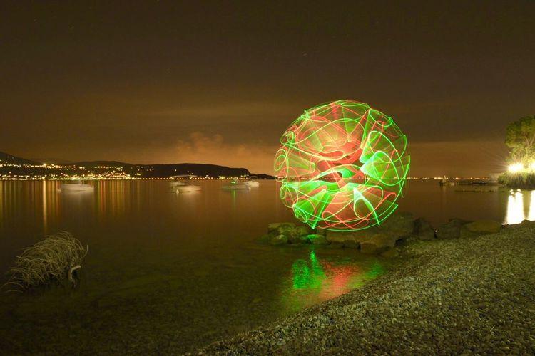Illuminated ferris wheel by lake against sky at night