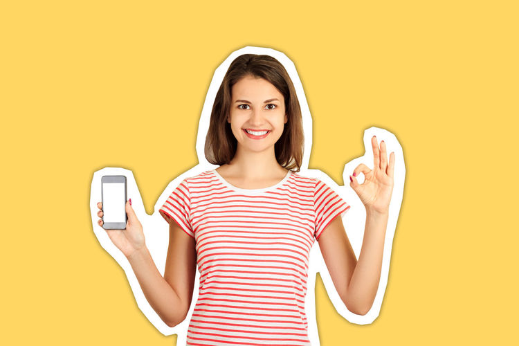 Portrait of a smiling young woman against yellow background