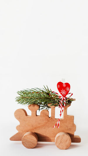 Close-up of christmas decorations on table against white background
