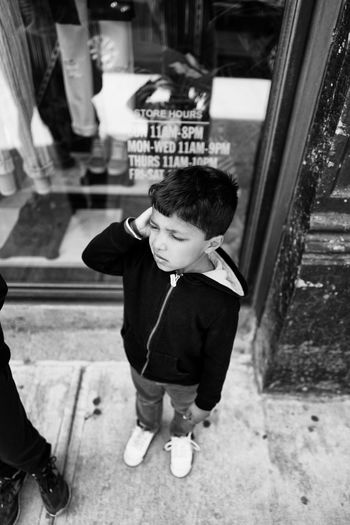 High angle view of confused boy standing outside store
