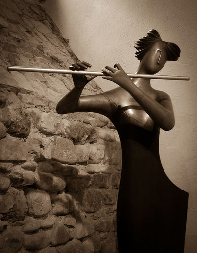 Flute player Suonatrice di flauto Gianfranco Giorni Anghiari, Toscana Gianfranco Giorni Beautiful Woman Beauty Flute Player Holding Indoors  Leisure Activity Lifestyles Rear View Rock Sculpture Solid Standing Stone Wall Three Quarter Length Wall - Building Feature