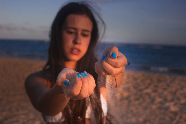 Teenage girl playing with sand at beach against sky
