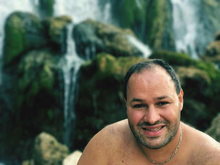 Portrait of shirtless happy man against waterfall