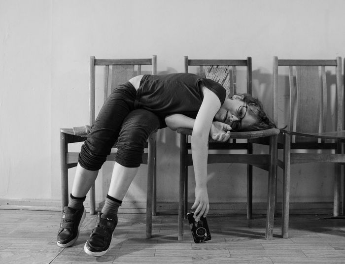 Portrait of boy lying on chairs