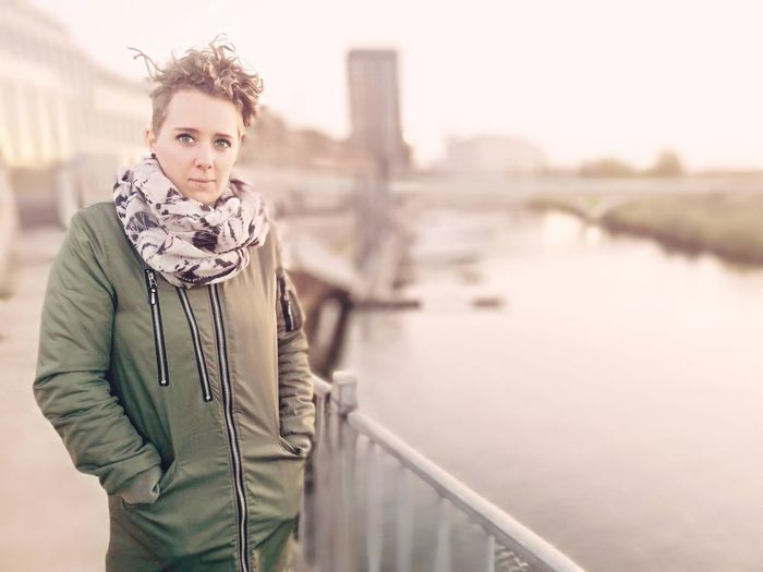 Portrait of woman wearing warm clothing while standing by river