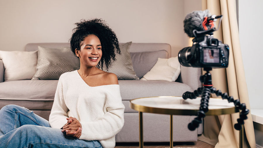 Vlogger Blogger Technology Sitting Indoors  Sofa Living Room Lifestyles Hairstyle Recording Video Content Social Media Looking At Camera One Person Real People Filming DSLR Mixed Race