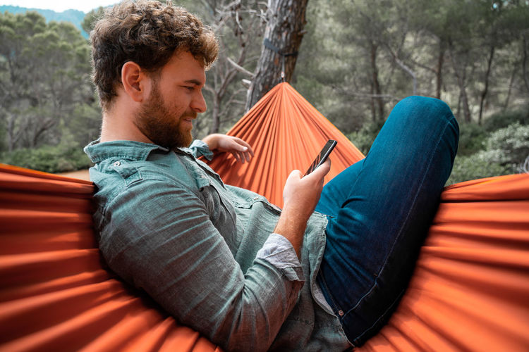 Man sitting using smart phone while on hammock in forest