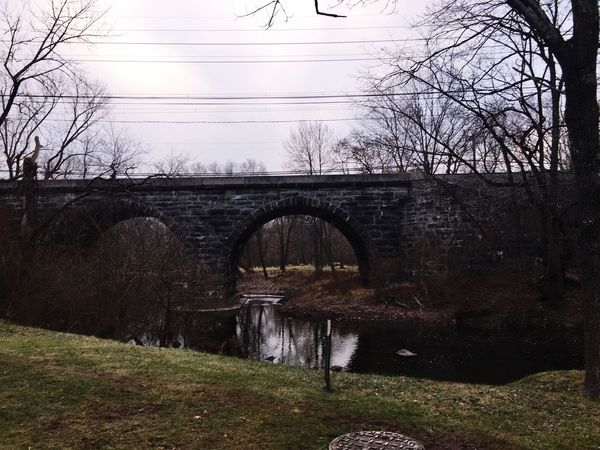 Bridges become frames for looking at the world around us. 🌚🌿 Green Ribbon Trail Photoshoot Grass Sky Transportation Outdoors Bridge Nature River Day Water Built Structure Tree Architecture Arch Bridge Bare Tree Arch Connection Bridge - Man Made Structure Pennslyvania Septa  2018