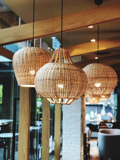 Low angle view of illuminated pendant lights hanging in restaurant