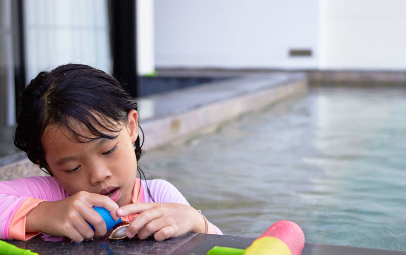 Portrait of girl play toy on poolside