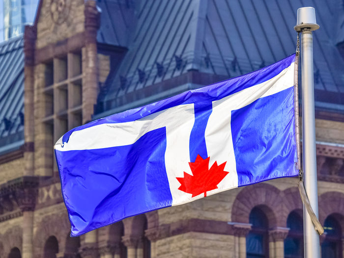 The flag of Toronto city waving in front of the Old City Hall City Toronto Canada Toronto Flag Waving Architecture Building Exterior Built Structure Close-up Day Flag Flag Of Toronto Flying No People Outdoors Symbol Symbolic  Toronto City