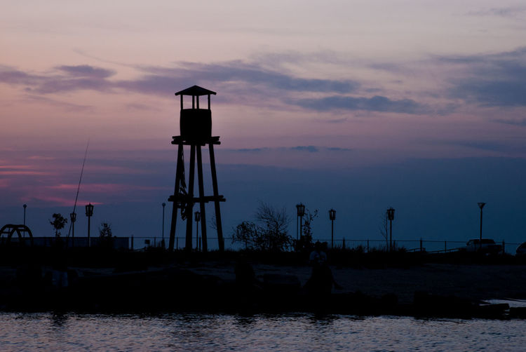 Silhouette water tower by sea against sky during sunset