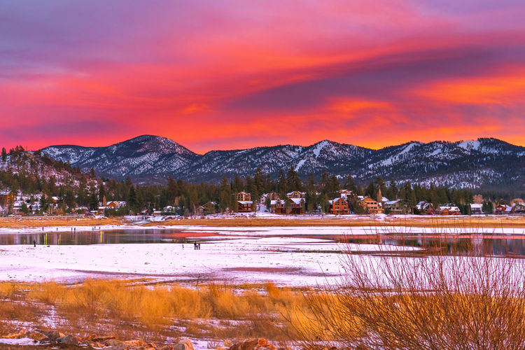 Scenic view of lake by snowcapped mountains against orange sky