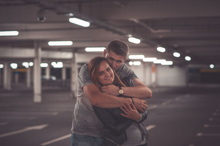 Portrait of couple embracing in parking lot