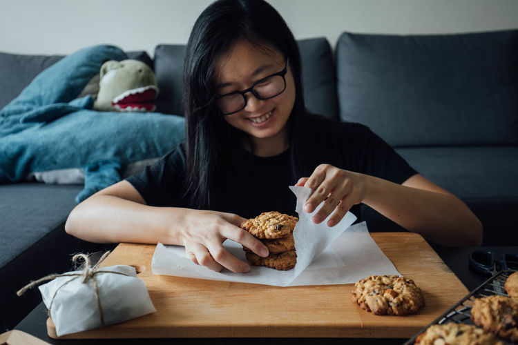 Young woman wrapping cookie while sitting by table at home