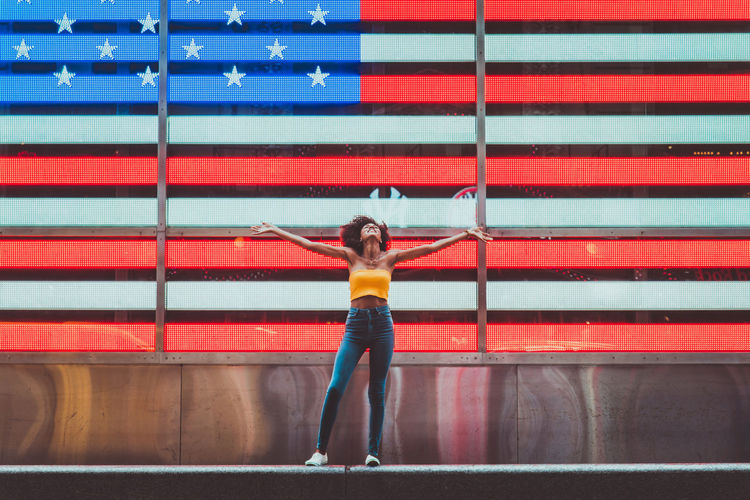 Full length of young woman standing with arms outstretched against neon american flag in city