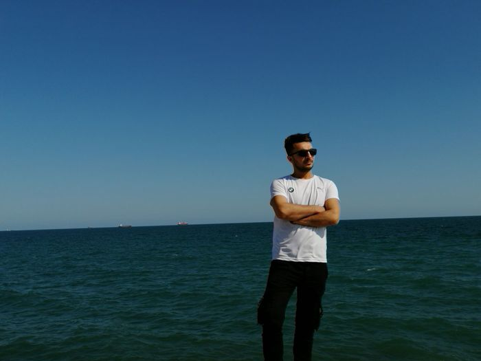 Portrait of man standing in sea against clear blue sky